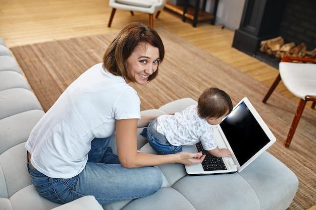 Madre moderna e creativa con bambini che fanno multitasking al mattino. mamma e bambino sono moderne tecnologie e gadget. lavorare a casa nel deviato.