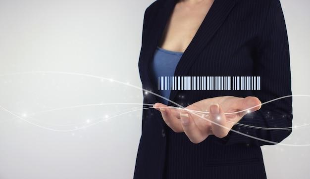 Concetto di produzione logistica di inventario. tenere in mano il codice a barre dell'ologramma digitale su sfondo grigio. moderne aziende di tecnologia di gestione del magazzino.