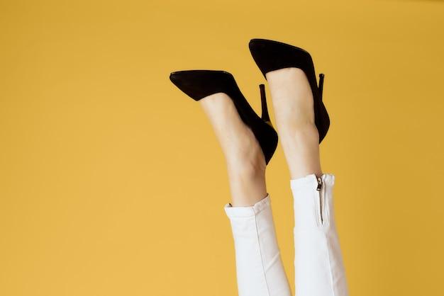 Gambe femminili invertite scarpe nere sguardo attraente sfondo giallo shopping