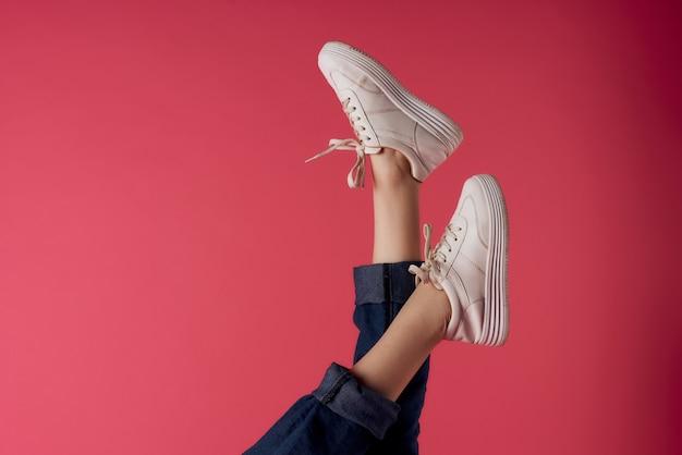 Piedini femminili invertiti in scarpe da ginnastica bianche sfondo rosa studio di moda
