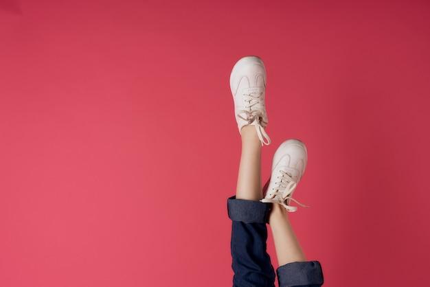 Gambe femminili invertite scarpe da ginnastica bianche movimento street style rosa