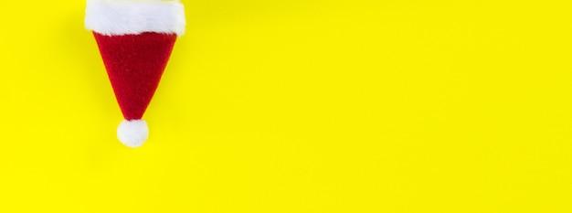 Cappello rosso di babbo natale invertito su sfondo giallo.