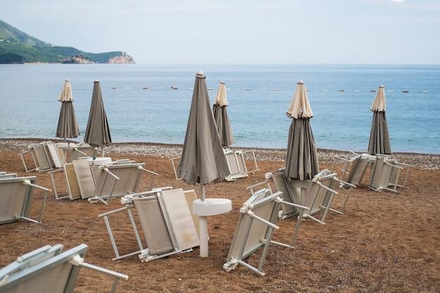 Lettini rovesciati sotto ombrellone sulla spiaggia di ciottoli in riva al mare
