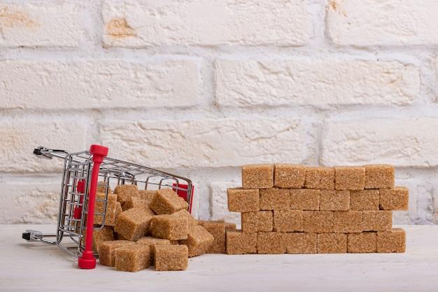 Carrello rovesciato con zucchero di canna di canna e un muro di loro cubetti di zucchero