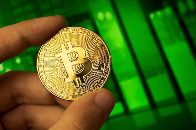 Investire in bitcoin sfondo concetto, moneta criptovaluta in mano close-up, verde grafico azionario foto