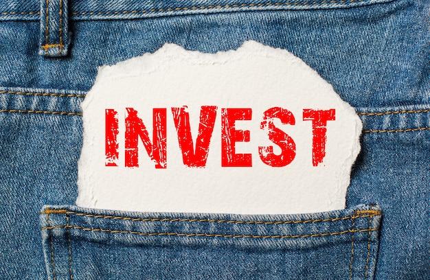 Investire su carta bianca nella tasca dei jeans blu denim