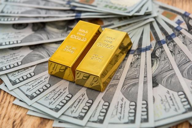 Investire in veri lingotti d'oro su banconote da un dollaro. denaro e risparmia concetto