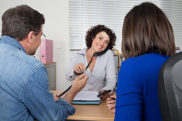 Consulente per gli investimenti che dà una presentazione a una coppia sorridente amichevole