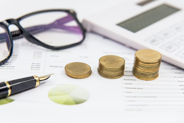 L'investimento per la pila di monete su carta analizza il grafico finanziario con calcola. concetto di investimento e risparmio