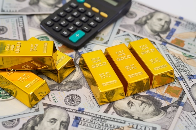 Successo di investimento o concetto di calcolo della ricchezza finanziaria, lingotti d'oro / lingotti su un mucchio di banconote in contanti in dollari usa con calcolatrice.