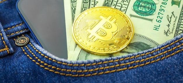 Sfondo banner di investimento e trading con primo piano bitcoin dorato, valuta criptata in una tasca di jeans blu, foto di dollari usa