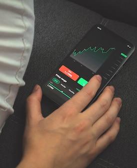 Investitore che analizza il grafico del mercato azionario sul telefono cellulare. schermo con grafici finanziari, foto concettuale di trading e scambio