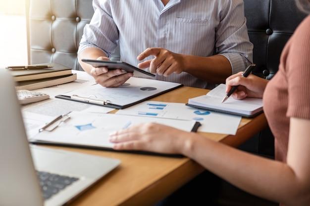 Colleghi esecutivi dell'investitore che discutono i nuovi dati finanziari del grafico di piano sulla tavola dell'ufficio