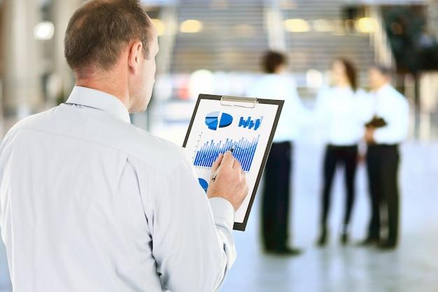 Investitore con l'analisi finanziaria del programma dei profitti dell'azienda.