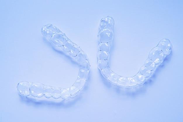 Denti dentali invisibili staffe allineatori dente su sfondo blu. apparecchi di contenzione in plastica per l'odontoiatria per raddrizzare i denti.