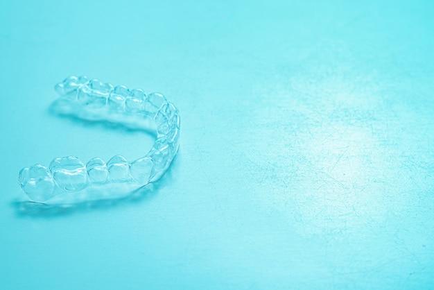 Denti dentali invisibili staffe allineatori dente su sfondo turchese. apparecchi di contenzione in plastica per l'odontoiatria per raddrizzare i denti.