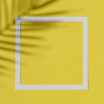 Invito o banner o poster con silhouette di ombra grafica ramo di palma e bordo cornice bianca su sfondo illuminante. fondo giallo di estate di colore pastello.