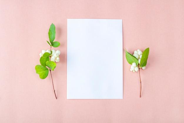 Mockup di carta di invito. cartolina d'auguri in bianco modello per il matrimonio, il compleanno e altri eventi. carta su sfondo color pesca con fiori bianchi. concetto di scrittura romantica per san valentino