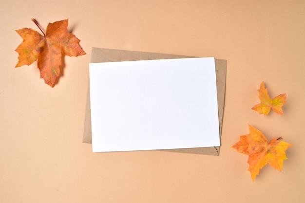 Modello di invito con una busta e foglie d'acero autunnali su fondo beige.
