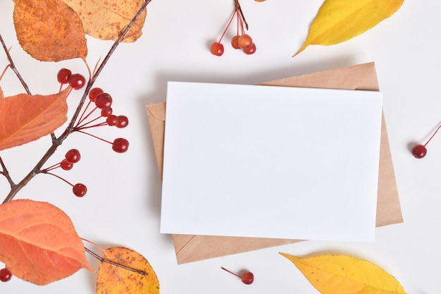 Modello di invito con una busta su fondo beige con un ramo autunnale di un melo. una nota romantica. layout piatto, vista dall'alto, un posto da copiare. layout piatto, vista dall'alto, un posto da copiare.