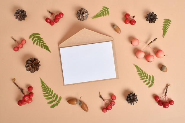 Modello di invito con una busta su fondo beige con vari oggetti naturali. layout piatto, vista dall'alto, un posto da copiare.