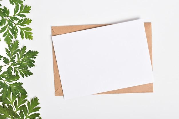 Modello di invito con una busta su uno sfondo bianco con oggetti di ramoscelli verdi. layout piatto, vista dall'alto, un posto da copiare.