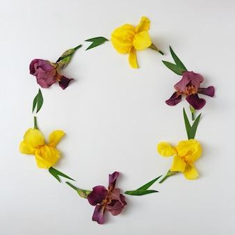 Invito con bordo e ghirlanda di iris gialli e viola. idea moderna della bandiera decorativa.