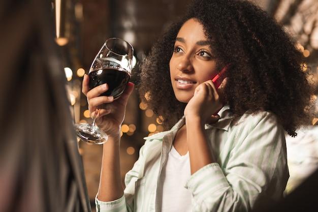 Invitando a bere. bella giovane donna seduta al bar, bevendo vino e avendo una conversazione telefonica con la sua amica, invitandola a bere qualcosa insieme