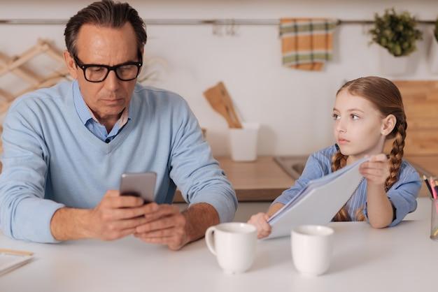 Uomo d'affari invecchiamento occupato coinvolto che utilizza gadget a casa e ignora il bambino mentre lavora e naviga in internet