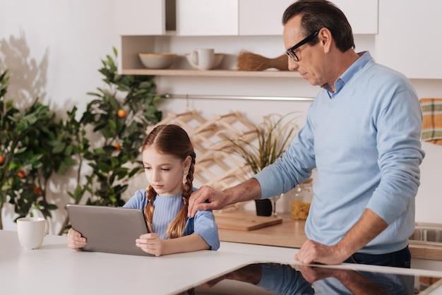 Uomo anziano premuroso coinvolto in piedi in cucina mentre esprime insoddisfazione e porta via il dispositivo digitale dalla piccola nipote