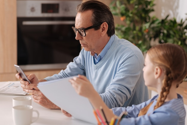 Uomo anziano indifferente coinvolto che utilizza un dispositivo digitale a casa e ignora il bambino durante la navigazione in internet
