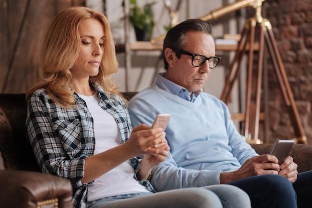 Coinvolta coppia matura catturata seduta sul divano a casa e utilizza il cellulare mentre naviga in internet ed esprime apatia