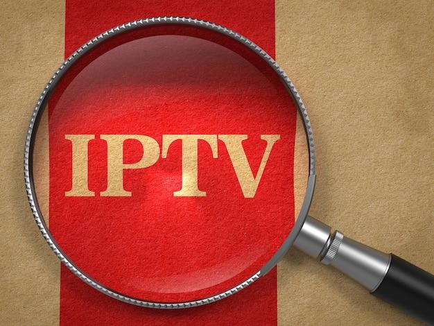 Concetto di iptv. lente d'ingrandimento su carta vecchia con sfondo rosso linea verticale.