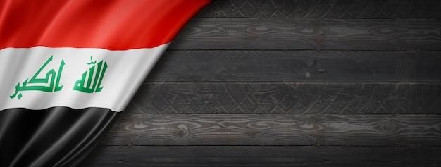 Bandiera dell'iraq sul muro di legno nero. banner panoramico orizzontale.