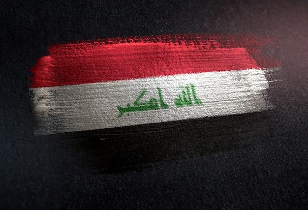 Bandiera iraq fatta di vernice pennello metallico sulla parete scura grunge