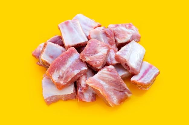 Costine di maiale crude su sfondo giallo