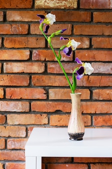 Fiore di iris in un vaso su un tavolo bianco sullo sfondo di un primo piano di un muro di mattoni