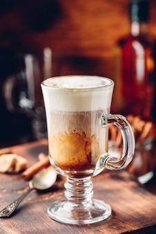 Caffè irlandese nel bicchiere su superficie di legno