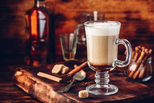 Irish coffee con cannella su superficie in legno