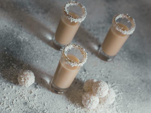 Crema irlandese o liquore al caffè con palline salutari di cocco fatto in casa e scaglie di cocco su sfondo chiaro