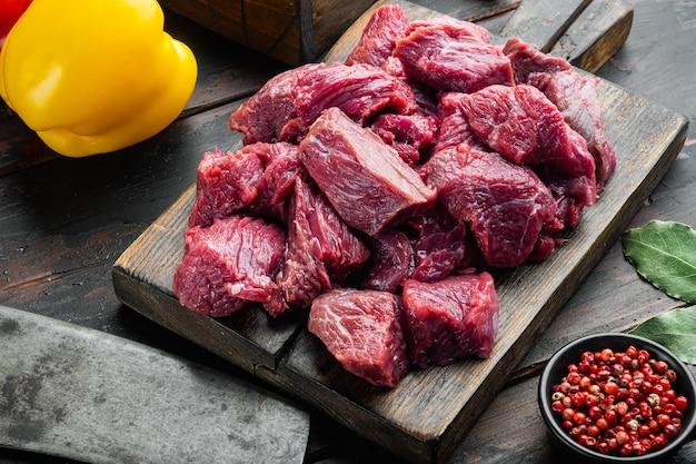 Ingredienti della ricetta dello stufato di manzo crudo irlandese con peperone dolce, sul vecchio tavolo di legno scuro