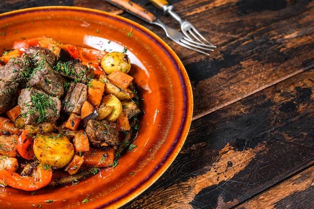 Stufato irlandese a base di carne di manzo, patate, carote ed erbe aromatiche. fondo in legno scuro. vista dall'alto. copia spazio.
