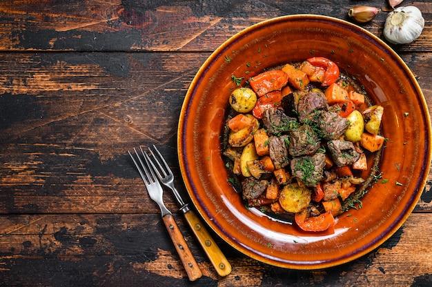 Stufato irlandese a base di manzo, patate, carote ed erbe aromatiche. fondo in legno scuro. vista dall'alto. copia spazio.