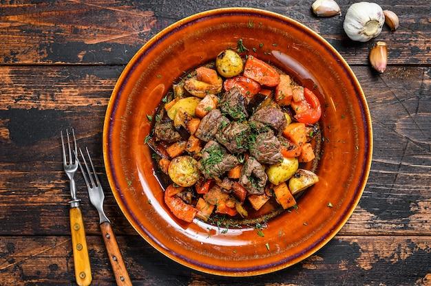 Stufato irlandese a base di carne di manzo, patate, carote ed erbe aromatiche. fondo in legno scuro. vista dall'alto.