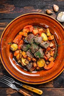 Stufato irlandese a base di manzo, patate, carote ed erbe aromatiche. fondo in legno scuro. vista dall'alto.