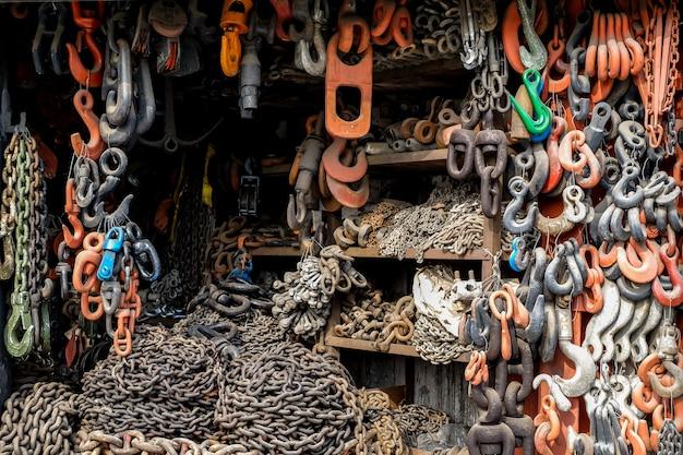 Catene di ferro con ganci giacciono e sono appese al negozio. un dispositivo per il carico e lo scarico delle merci.