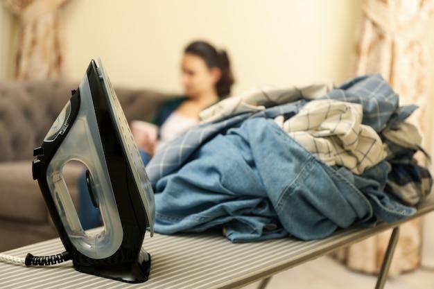 Ferro da stiro e biancheria sgualcita contro la donna seduta sul divano