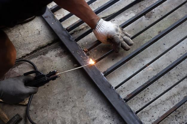 Riparazione del cancello di ferro, acciaio per saldatura a mano dell'operaio