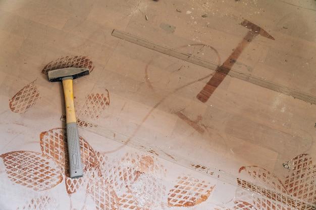 Il martello di ferro giace sul pavimento polveroso