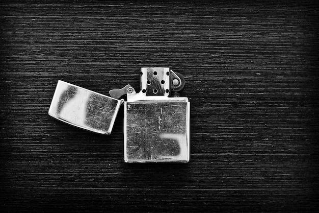Accendino di ferro su un tavolo di legno scuro in bianco e nero